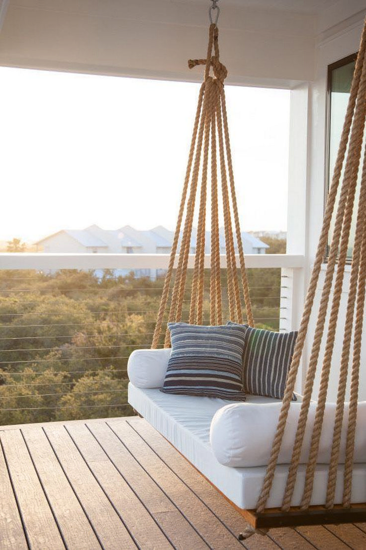 Covered Patio with Rope Swing Bed -Chic covered second floor balcony is  fitted with a rope swing bed adorned with plush white cushions and blue  striped ...