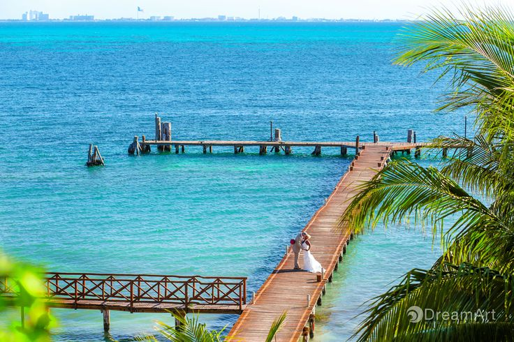 Newlywed couple stand on a pier surrounded by the turquoise Caribbean Sea at Isla Mujeres Palace @palaceresorts Photo courtesy of #DreamArtPhotography #DreamArtWedding #WeddingPhotography Special thanks to @prweddings