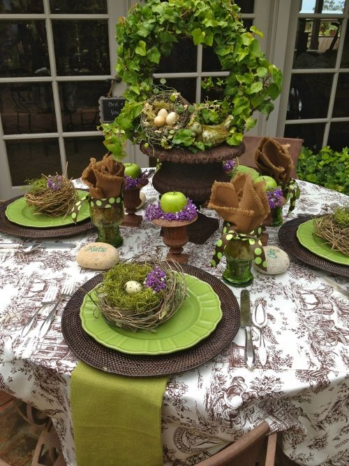 GREEN CABBAGE: Easter table with brown toile cloth, brown woven mats, green napkins, brownish urn and ivy centerpiece, and nests.