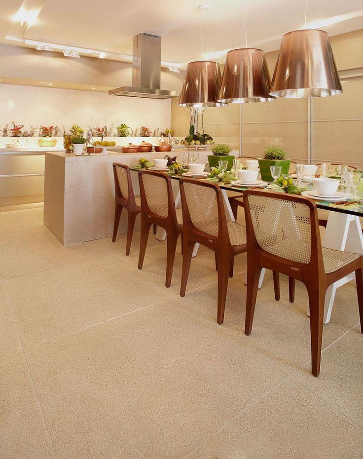 Espaço Gourmet com ilha e coifa suspensa, ambiente clean e chic, tons claros e piso Castelatto Crystalli. Iluminação com pendentes