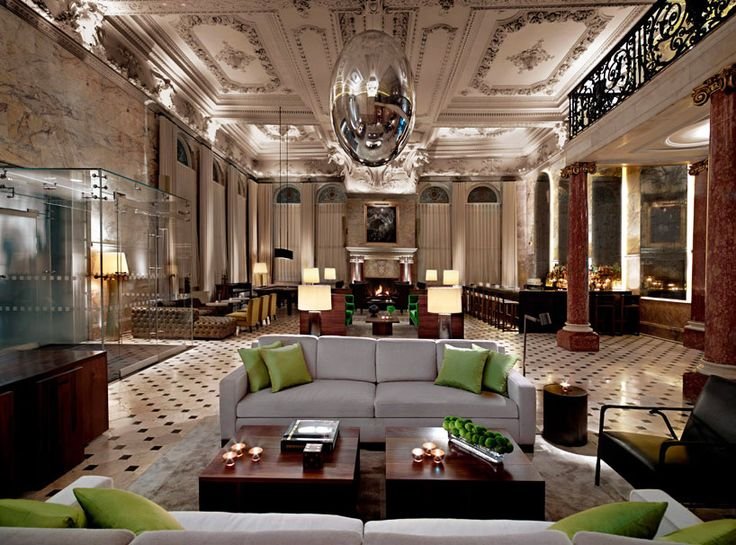 The Latest Hotel From Ian Schrager has black and white checkered tile flooring, ornate coffered ceilings, marble columns, leather couches, a large bar area, and hanging chrome orbs.