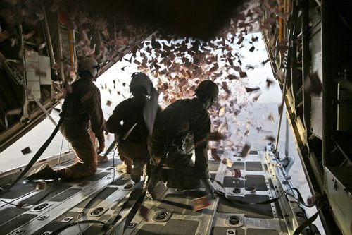 U.S. Marine Corps Cpl. Jameson Dudley, left, crew master with Marine Aerial Refueler Transport Squadron 252 (VMGR-252), and U.S. Army Sgt. Nijoku Odom, right, intelligence analyst with 303rd psychological operations company (303rd POCO), throw leaflets from a KC-130 Super Hercules over southern Afghanistan, Aug. 28, 2013. Leaflets were dropped in support of operations to defeat insurgency influence in the area.