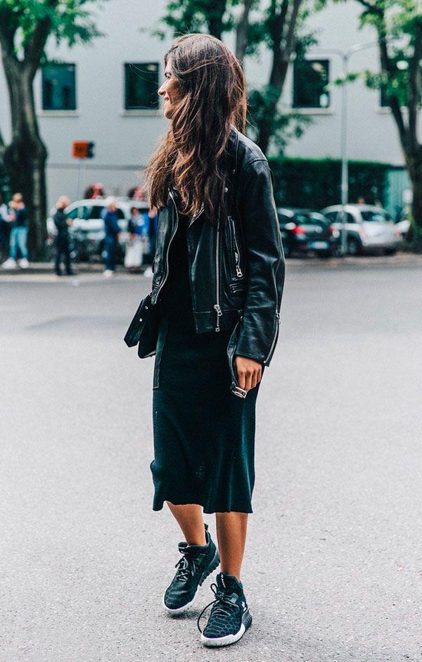 Street style look vestido preto, jaqueta couro preta e tênis.