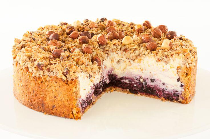 Borůvkový cheesecake V korpusu z máslovych sušenek se snoubí chuť borůvkového pyré a nadýchaného sýra Philadelphia. Dort je dozdoben lísko oříškovou drobenkou a celými lískovými oříšky.