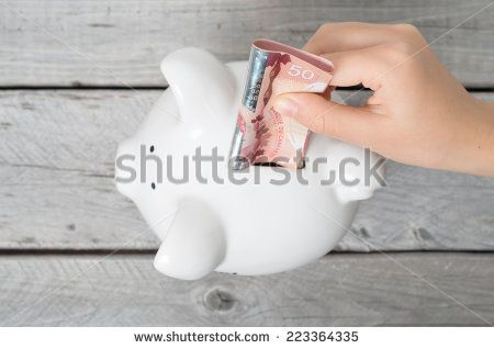 Asian boy hand inserting a fifty dollars bank note into white piggy bank  against wooden grey background - stock photo