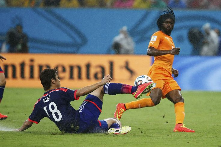 Japan's Yuya Osako (L) fights for the ball with Ivory Coast's Gervinho during their 2014 World Cup Group C soccer match at the Pernambuco ar...