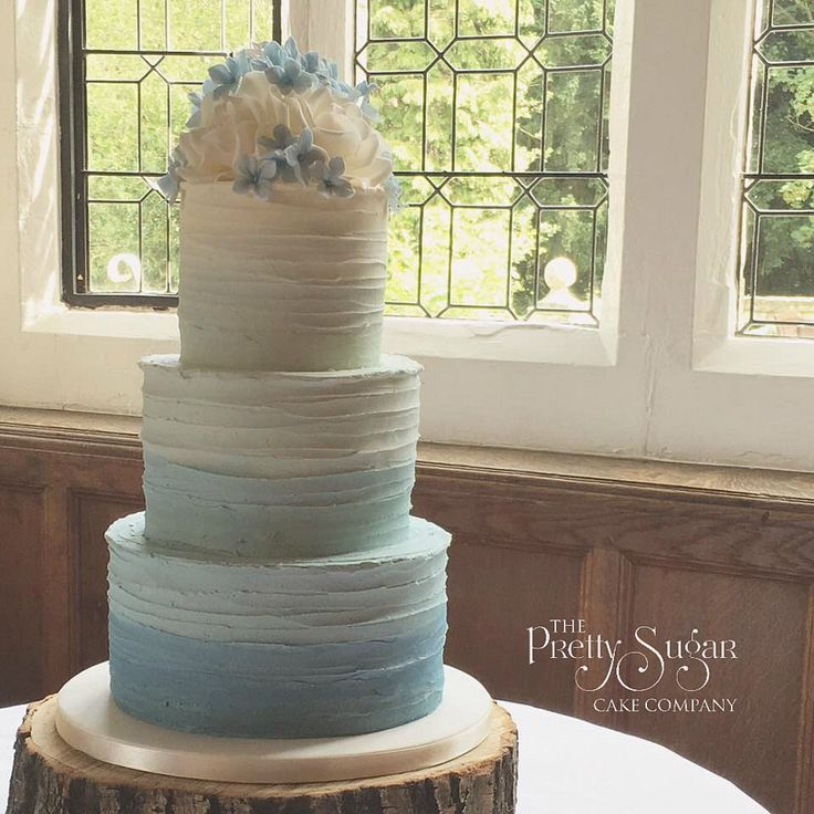 Blue ombré buttercream wedding cake with ivory sugar roses and blue hydrangea