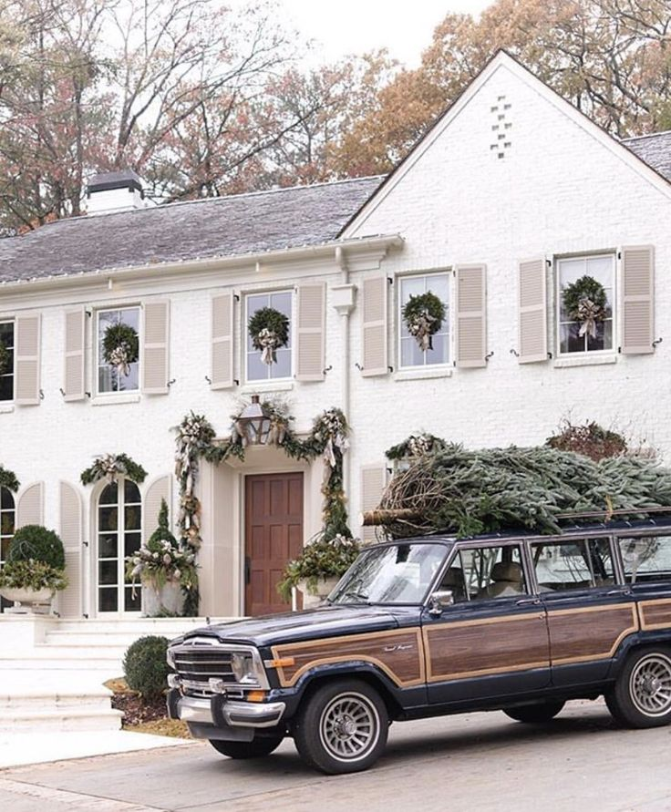 Live Christmas tree on jeep in front of gorgeous white house with wreaths on windows - Christmas goals!