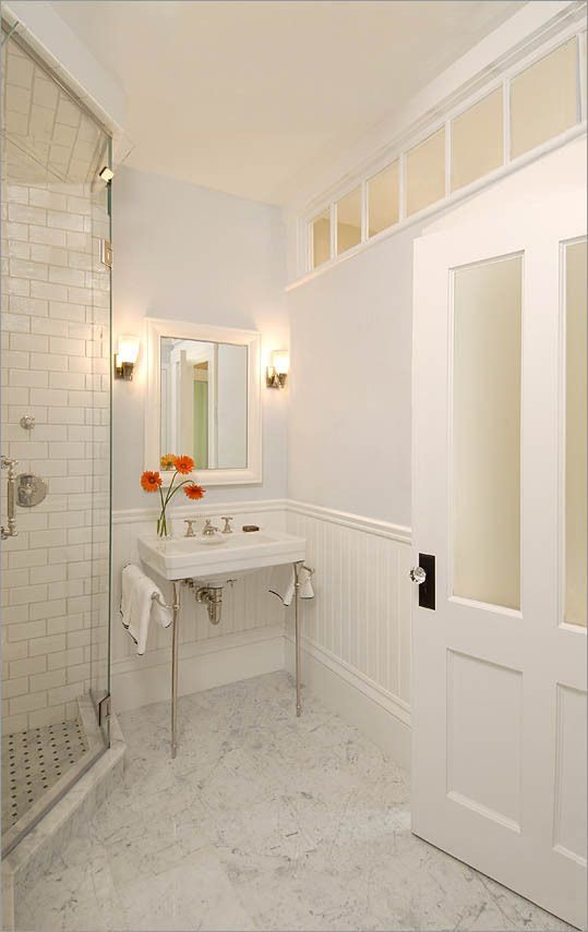 Transom windows at the ceiling and frosted glass door panels allow natural light from the hallway to reach a bathroom located along an interior wall. (charlie allen restorations)