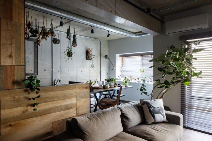 コンクリートの壁と、塗装の壁両方が存在するリビングダイニングです。 ダクトがむき出しで無機質な空間になりがちですが、キッチンの壁には木板、それから部屋に多用されたグリーンで、ぬくもりの感じられる空間になっています。 すべてをコンクリート打ちっぱなしにするのではなく、窓の周辺に塗装壁を用いることで無機質な印象が少し和らいでいますよね。リフォーム・リノベーション会社:株式会社クラフト「ヴィンテージもモダンもなじむ、ニュートラルな空間」