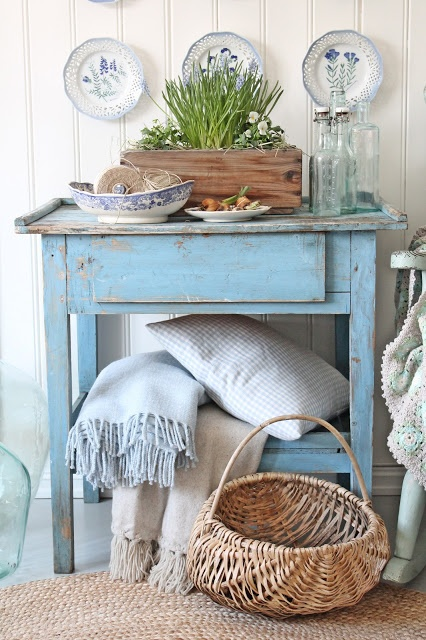 pillows and blankets cozy up a vintage painted table
