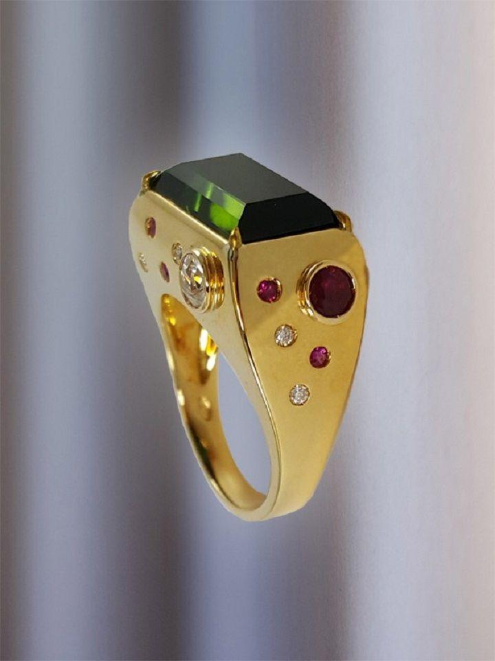 Artigiano: Alta Giolleria ItalianaAnello tormalina verde provenienza Namibia taglio smeraldo. Montatura in oro giallo con fianchi incastonati con pietre di differente caratura tra diamanti e rubini naturali.