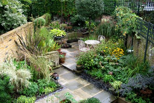 A small, narrow space feels larger when divided diagonally. Strong structural planting creates the bones of a garden through the seasons.
