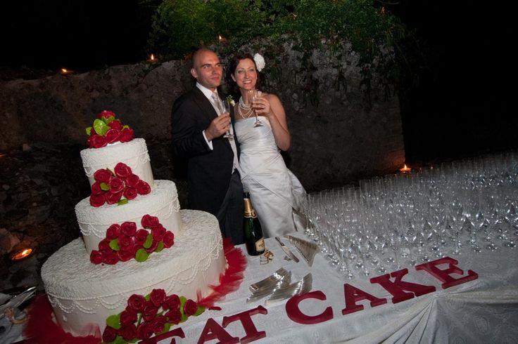 Bianco e rosso: una cascata di fiori sulla torta candida, ideale per matrimoni o cerimonie estive.