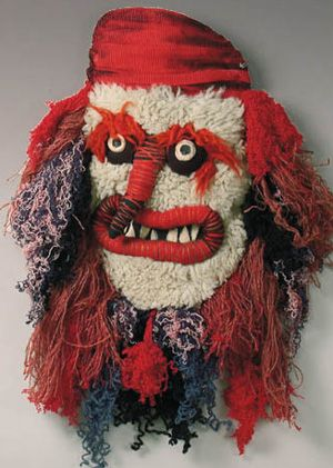 European Folk mask. Parau, Romania. Wool yarn with cloth, fur and beans.  A style of traditional Christmas or New Year mask from the area of Transylvania. It is almost flat and has no eye holes, it was to be held by hand in front of the face.