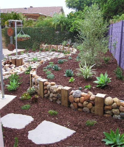 Homemade Gabion wall ie rocks encased in wire baskets & used as a retaining wall - creates a dramatic feature in a garden :)