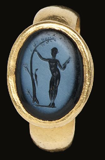 A ROMAN GOLD AND NICOLO FINGER RING   circa 1st century a.d.   The wide hoop flat on the interior, convex on the exterior, widening slightly at the shoulders where it joins the conical bezel, the oval stone delicately engraved with a representation of the Apollo Sauroktonos, the youthful god shown standing and leaning gracefully on a tree while aiming a dart held in his right hand at the tiny lizard which clambers up the tree trunk  size 10