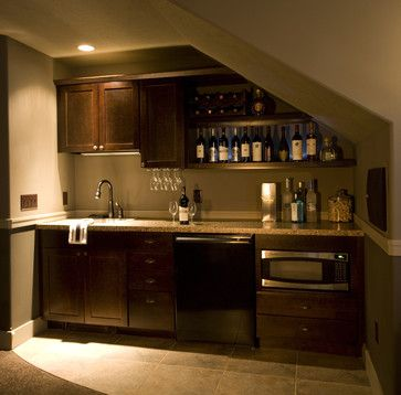 The void below a staircase offers a nice opportunity for a kitchenette in a duplex or finished basement. This kitchenette has a sink, microwave, dishwasher and wet bar. houzz.com