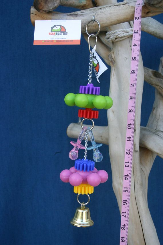 This toy features assorted brightly colored sprockets, small sprogs, and adorable baby pacifiers with a liberty bell. This bird toy should keep your birds beak busy for hours! This toy is perfect for larger small size birds (love birds, conures, caiques, cockatiels, even small species macaws and amazons, etc.). Toy measures approximately 15 inches tall. This toy was constructed with love, perfection and safety in mind for your feathered friend.  This is a new toy. All bird toys are handmade…
