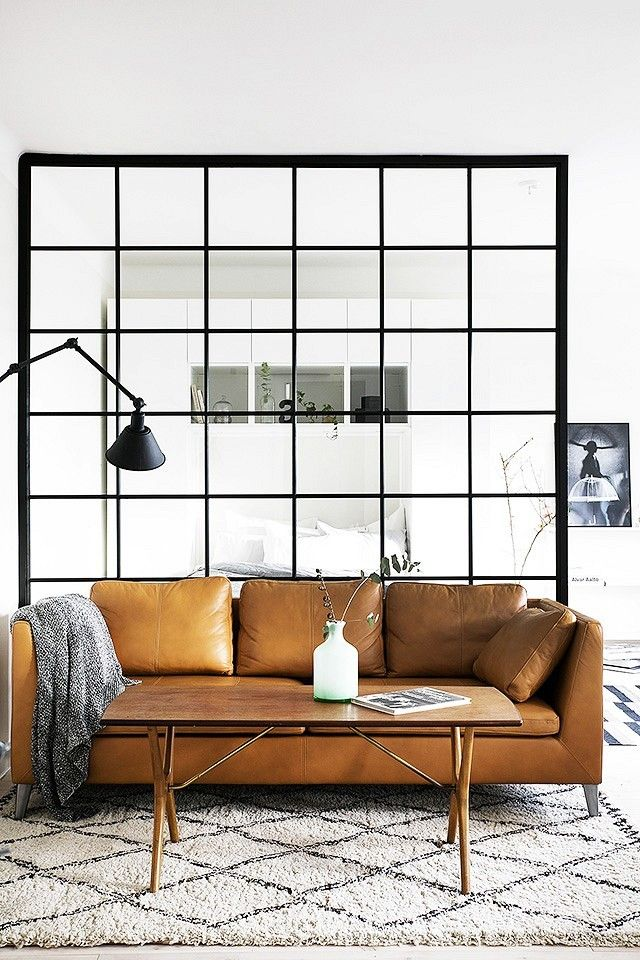 Swedish living space with a metal space divider and a leather sofa