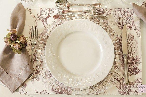 Para compor a mesa, louça limoges branca sobre belíssimos sousplats de cristal e jogos americanos em toile de jouy nos tons branco e vinho, harmonizando com os guardanapos e porta-guardanapos nos tons uva.