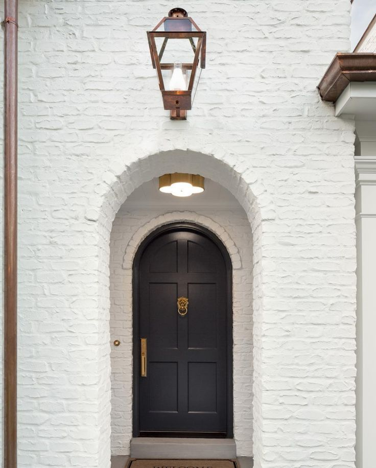 White Brick Exterior Bronze Lantern Sconce Rounded Archway Round Arched Front Door With Knocker And Gold Design