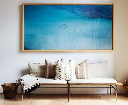 This photograph adds colour to a blank living room wall; neutral pillows made of vintage rugs help it fit in.