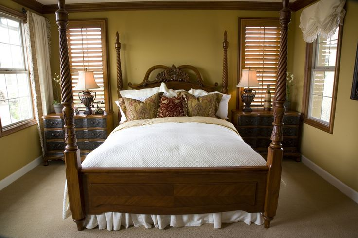This compact bedroom makes use of its space with classic wood bed frame with spiral posts, twin dark wood dressers and wood molding and window frames against tan walls and flooring.