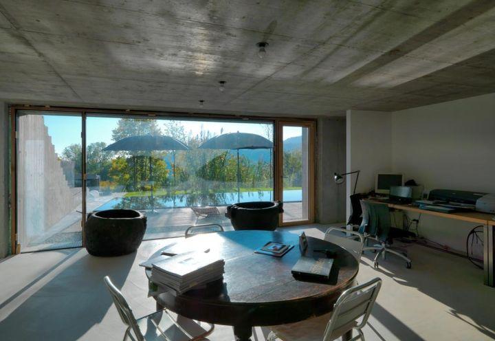 Il seminterrato di House Y comprende un ambiente-studio, arredato in maniera informale. La vista sulla piscina e le colline rilassa la vista