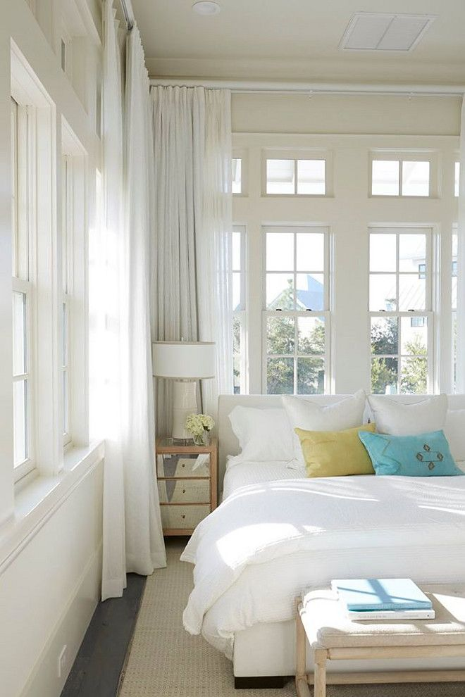 Beach Style Bedroom. This coastal bedroom is decorated with a white upholstered bed dressed in green and blue velvet pillows and a small mirrored nightstand. Wall of windows are dressed in white curtains. cottage-bedroom Geoff Chick & Associates