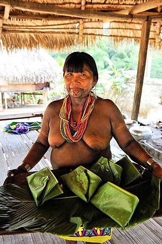 Mujeres que ofrecen platos de pescado envuelto en hojas, Embera comunidad nativa  al lado del río Chagres dentro del Parque Nacional Chagres, República de Panamá, América Central