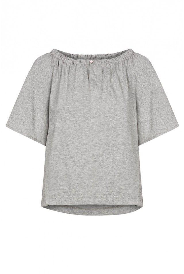 Bluzka wykonana z dzianiny bawełnianej. Lekko poszerzana, tył lekko dłuższy. Rękawy do łokcia, również poszerzane. Dekolt w gumkę. Po środku ozdobny kamyczek.