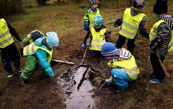 """Kartanonkosken päiväkodin Auringonkukat-kerhon 4–5-vuotiaiden ryhmä retkeilee perjantaisin lähimetsään Tammiston luonnonsuojelualueelle. Metsässä tutkittiin luupeilla kääpää ja leikittiin kepeillä. Retkellä voidaan myös laulaa ja loruilla. """"Täällä ei tarvitse ohjailla liikkumiseen, vaan tasapainoilua tulee ihan luonnostaan"""", sanoo lastentarhanopettaja Sirpa Markkanen."""