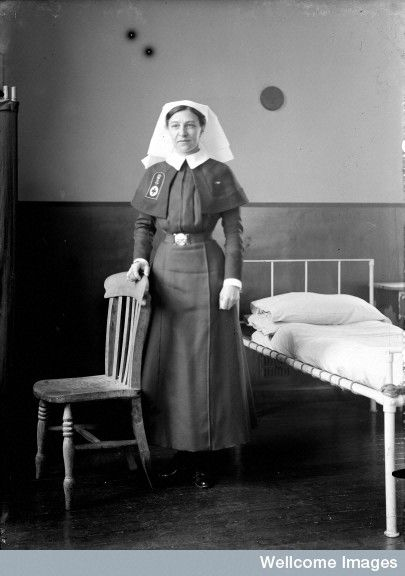 Matron Miss Hickley standing in a ward, ca. 1919.