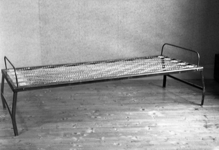 Foto av en enkel järnsäng med resårbotten. 1938  Ateljéfoto.