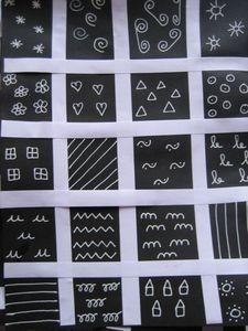 Graphisme blanc sur fond noir.  Collage de bandes de papier blanc pour délimiter le quadrillage, graphisme en blanc sur les carrés restants.
