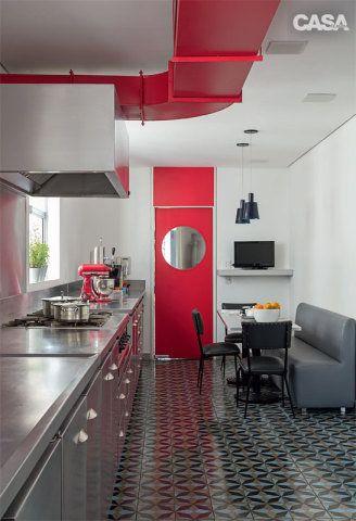 Na cozinha com piso de ladrilho hidráulico (Dalle Piagge), a tubulação da coifa industrial, grande demais   para embutir, fcou aparente no teto, pintada de vermelho. No cantinho junto à porta vaivém, a família faz as refeições do dia a dia. Luminárias da Bertolucci.