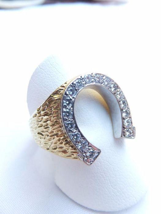 """Een robuuste 18 karaat heren ring """"HOEFIJZER"""" in bi-color bezet met 17 briljant geslepen diamanten Europa rond 1970.  Een robuuste 18 karaat heren ring """"HOEFIJZER"""" in bi-color bezet met 17 briljant geslepen diamanten In nieuw staat in bi-color goud 18k 750/1000 bezet 17 briljant geslepen diamanten totaal 05 crt. in de kwaliteit """"Wessel Ton"""" VSIringmaat 21. maat hoefijzer 146 x 162 m.m. gewicht 138 gram.Ring verkeert mint conditie en wordt geleverd in afgebeeld luxe etui.per aangetekende post…"""