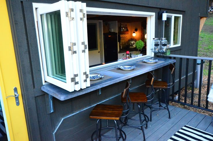 This small kitchen window opens up to the outside patio, where stools welcome guests for a bbq. | Tiny Homes