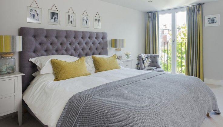 A row of favourite black-and-white prints helps to personalise the grey and yellow bedroom in this victorian home. The slipper chair picks up on the button detail of the impressive headboard, while the matching bedside tables, table lamps and scatter cush
