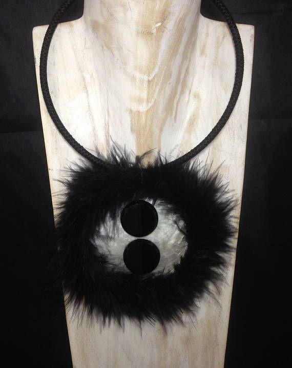collier ras de cou. médaillon en nacre ,bordé de duvet de cygne ,au centre deux boutons anciens en verre. finition passementerie. pièce unique diamètre du médaillon 8 cm diamètre tour de cou 14,5 cm variable car le tour de cou sécarte