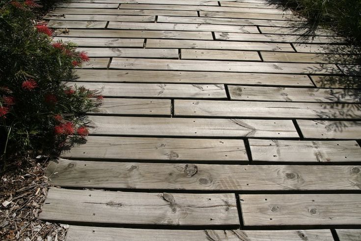 Think of alternatives to stone and concrete paving. Hardwood timber sleepers fixed to a concrete slab driveway add texture, tone with native plantings & direct runoff to surrounding gardens. Design Jessup & Elkan