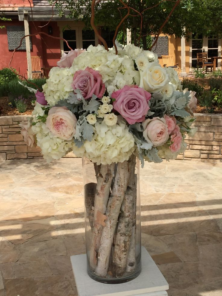 Ceremony flowers with open roses and hydrangea.  Love the birch poles in the cylinder vase.