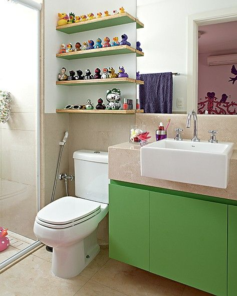 O banheiro é clássico, revestido de mármore travertino. Mas o verde do móvel abaixo da pia e as prateleiras com patinhos em toy art garantem o clima de diversão no projeto da arquiteta Bruna Riscali