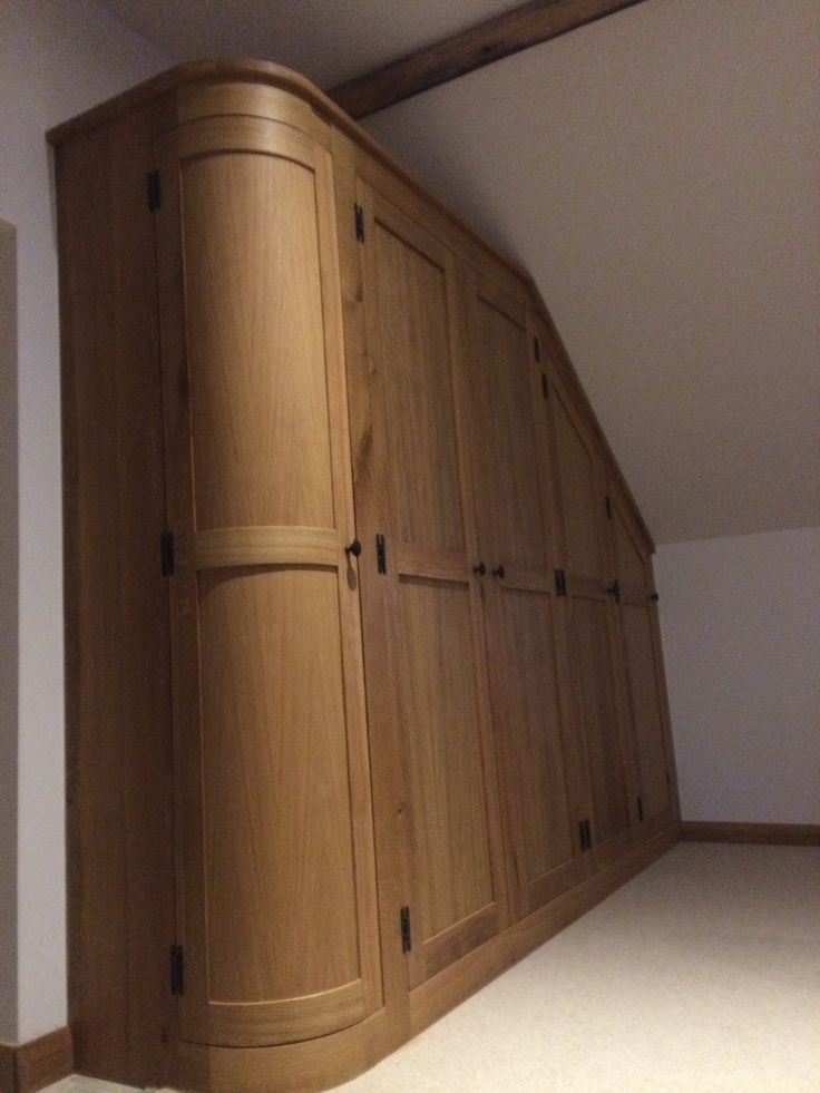Curved cupboards create a softer feel to this wardrobe within this fitted  dressing room. The
