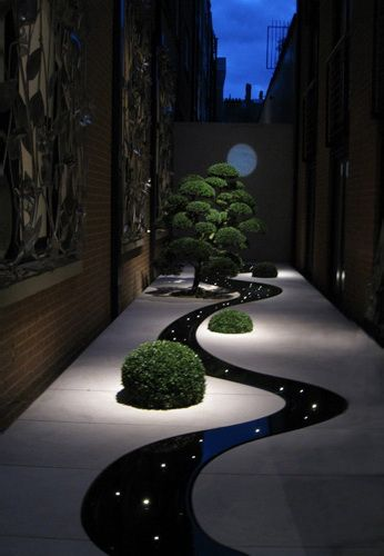 """stone courtyard with bushes and small tree, weave water through """"river"""" place candles under river"""