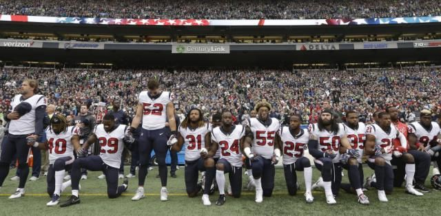 Houston Texans players kneel and stand during the singing of the national anthem before an NFL football game against the Seattle Seahawks, Sunday, Oct. 29, 2017, in Seattle. (AP Photo/Elaine Thompson)
