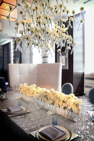 Locally grown white carnations presented in finger vases on matrix silver and light blue lamour set beneath a chandelier of strung vases of carnations.