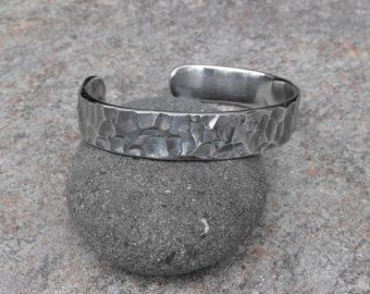 """Spiral cuff . For a limited time, Im offering shipping for $1 with this listing!! This spiral cuff has a brand new look that is out of this world! It combines 2 different finish styles. A matte influence and then its extenuation of a fantastic contrasted light polishing that grabs its elegant yet rustic glowing affect. Material specifications for this cuff are, ¼"""" by ¼"""" square rod, grade 304 stainless steel.  When ordering one of my bracelets, please measure your wrist in inches with a cloth…"""