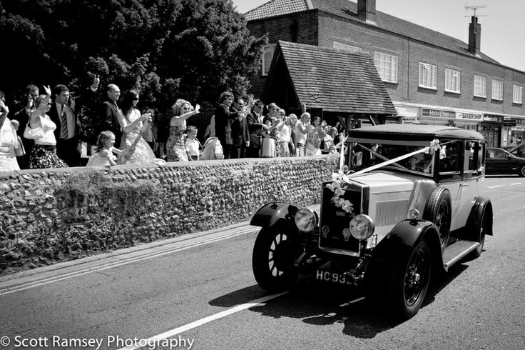 Wedding guests wave as the Bride and Groom leave in a vintage car after getting married in Rustington, West Sussex, UK. Photo by Scott Ramsey Photography http://scottramsey.co.uk/blog/2013/12/28/rustington-wedding-photography-a-summer-church-wedding
